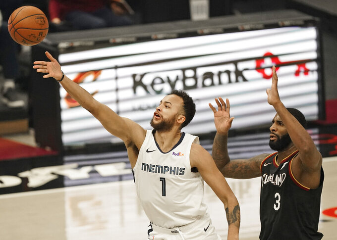 Memphis Grizzlies' Kyle Anderson (1) drives to the basket against Cleveland Cavaliers' Andre Drummond (3) in the first half of an NBA basketball game, Monday, Jan. 11, 2021, in Cleveland. (AP Photo/Tony Dejak)