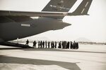 In this image provided by the U.S. Marine Corps, evacuees wait to board a Boeing C-17 Globemaster III during an evacuation at Hamid Karzai International Airport in Kabul, Afghanistan, Monday, Aug. 30, 2021. (Staff Sgt. Victor Mancilla/U.S. Marine Corps via AP)