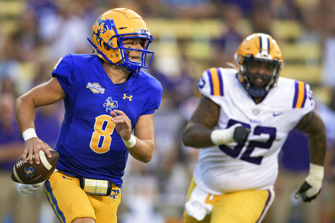 McNeese State quarterback Cody Orgeron (8) runs against LSU defensive lineman Neil Farrell Jr. (92) during the first half of an NCAA college football game in Baton Rouge, La., Saturday, Sept. 11, 2021. (AP Photo/Matthew Hinton)