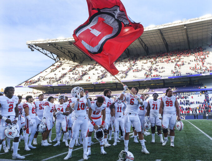 Utah defensive end Bradlee Anae (6) waves a flag as he and teammates celebrate after an NCAA college football game against Washington, on Saturday, Nov. 2, 2019, in Seattle. Utah won 33-28. (AP Photo/Stephen Brashear)