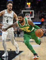 Boston Celtics' Kyrie Irving, right, drives against San Antonio Spurs' Derrick White during the first half of an NBA basketball game, Monday, Dec. 31, 2018, in San Antonio. (AP Photo/Darren Abate)