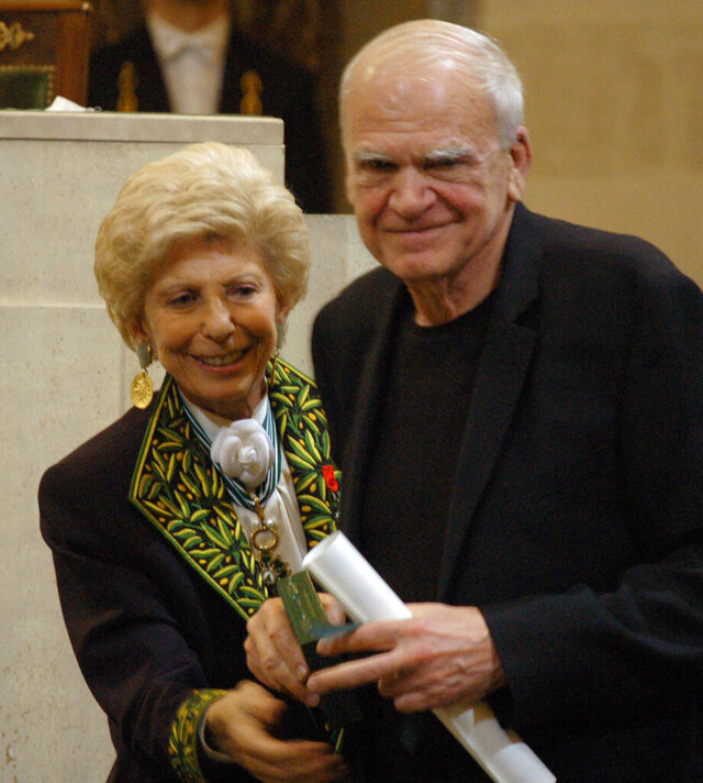 FILE - In this  June 10, 2009, file photo, Czech-born author living in France Milan Kundera, right, is awarded the Simone and Cino Del Duca Foundation World Prize for his lifetime achievement in Paris, France. On the left is French political historian Helene Carrere d'Encausse. Kundera has regained Czech citizenship after 40 years, daily Pravo writes on Tuesday, Dec. 3, 2019, adding that Czech ambassador Petr Drulak handed the relevant document to him in his Paris apartment on November 28. (Remy Vlachos/CTK via AP)