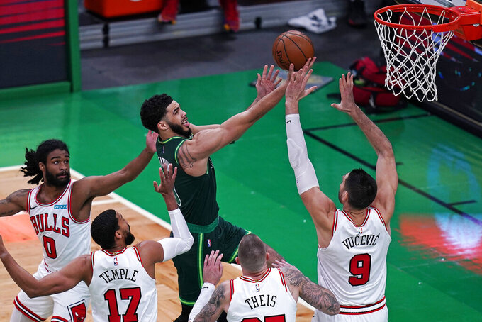 Boston Celtics forward Jayson Tatum, center, drives to the basket against the Chicago Bulls defense during the first half of an NBA basketball game, Monday, April 19, 2021, in Boston. (AP Photo/Charles Krupa)