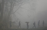In this Jan. 15, 2020, photo, Nepalese men carry logs of wood for a cremation, enveloped in thick morning fog in Bhaktapur, Nepal. (AP Photo/Niranjan Shrestha, File)