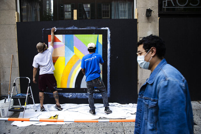 Workers affix a poster to a shuttered business in Philadelphia, Monday, May 4, 2020. The Center City District and Mural Arts Philadelphia posted the original works on multiple locations in an effort to enhance the neighborhood awash with business shuttered to help curb the spread of coronavirus. (AP Photo/Matt Rourke)
