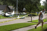 A small aircraft sits in the front yard of a home Tuesday, July 28, 2020, in Houston. Two people were injured when the single-engine airplane crashed in a residential area early Tuesday, authorities said. The airplane hit a tree and landed shortly before 2 a.m. (Brett Coomer/Houston Chronicle via AP)