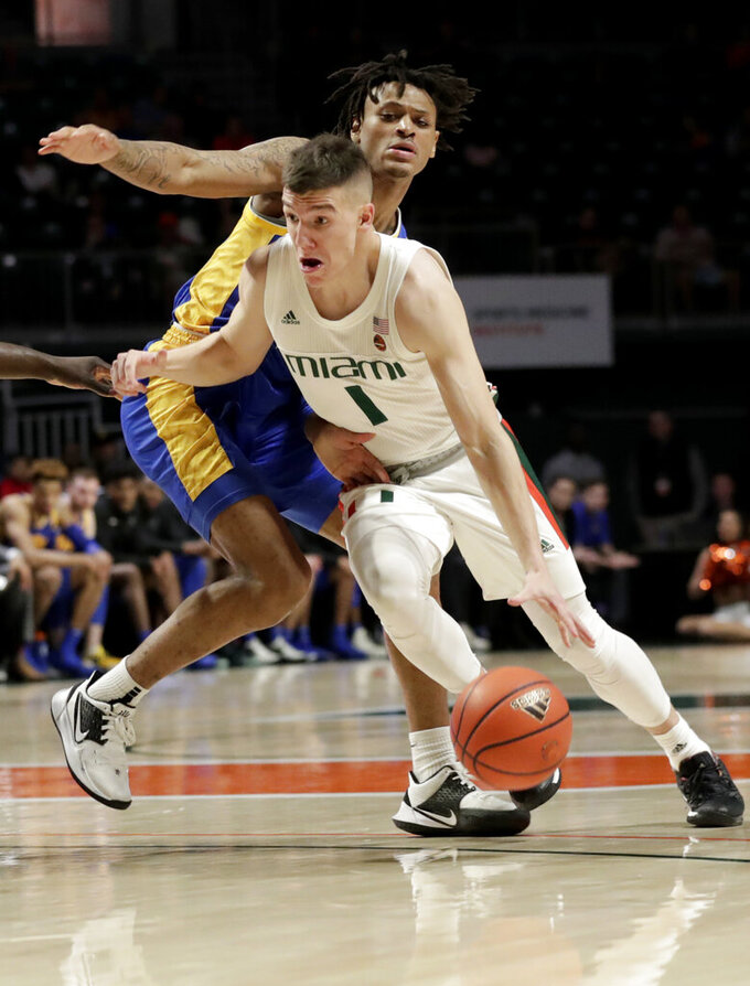 Miami guard Dejan Vasiljevic (1) drives to the basket as Pittsburgh guard Au'Diese Toney defends during the second half of an NCAA college basketball game, Sunday, Jan. 12, 2020, in Coral Gables, Fla. (AP Photo/Lynne Sladky)