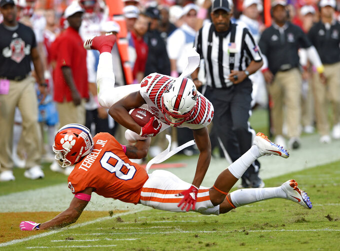 North Carolina State's C.J. Riley(19) is upended by Clemson's A.J. Terrell during the second half of an NCAA college football game, Saturday, Oct. 20, 2018, in Clemson, S.C. (AP Photo/Richard Shiro)