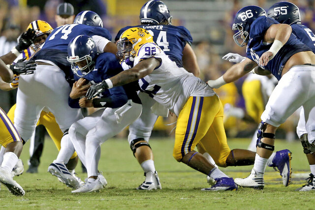 FILE - LSU defensive end Neil Farrell Jr. (92) sacks Georgia Southern quarterback Justin Tomlin (17) in the fourth quarter during an NCAA college football game in Baton Rouge, La., Saturday, Aug. 31, 2019. LSU coach Ed Orgeron says defensive lineman Neil Farrell has rejoined the team after initially opting out more than a month ago. But the 6-foot-4 and 319-pound Farrell's readiness for the season opener against Mississippi State on Sept. 26 remains to be seen. (AP Photo/Michael Democke, File)
