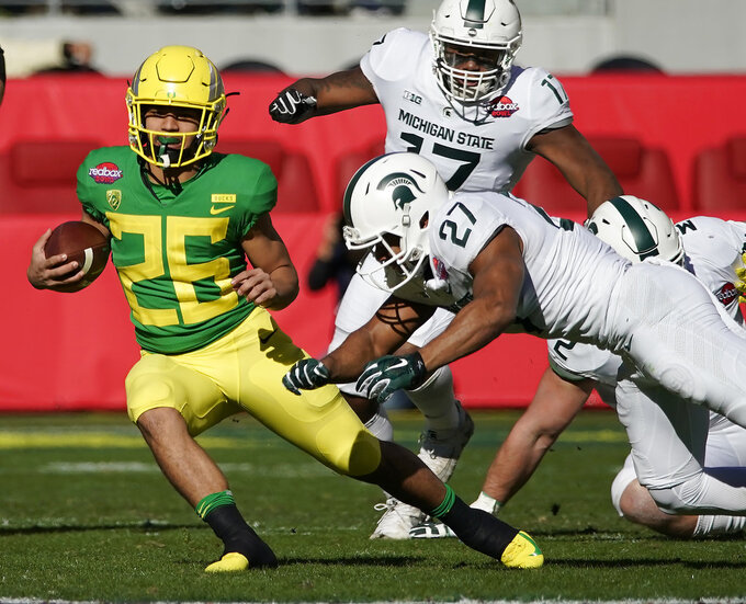 Oregon Ducks running back Travis Dye (26) rushes for a first down past Michigan State Spartans safety Khari Willis (27) during the first half of the Redbox Bowl NCAA college football game Monday, Dec. 31, 2018, in Santa Clara, Calif. (AP Photo/Tony Avelar)