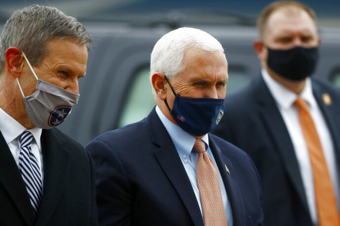 Vice President Mike Pence, right, and Tennessee Gov. Bill Lee talk on the tarmac at the Air National Guard 164th Airlift Wing prior to a roundtable discussion about Operation Warp Speed on Thursday, Dec. 3, 2020, in Memphis, Tenn. (Joe Rondone/The Commercial Appeal via AP)