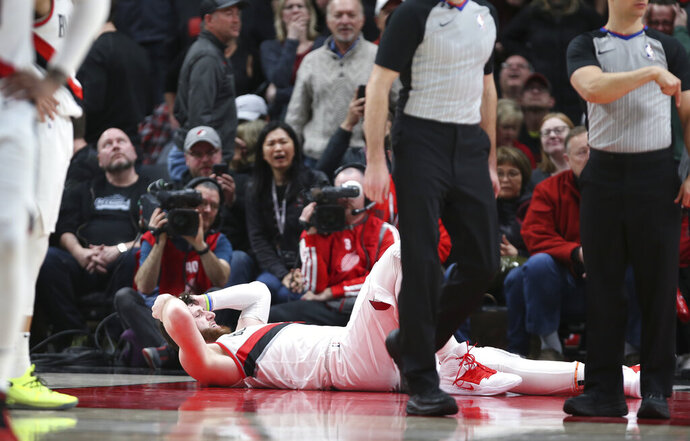 Portland Trail Blazers center Jusuf Nurkic, on ground, was injured and left the court on a stretcher as the Blazers beat the Brooklyn Nets in double overtime, 148-144, during an NBA basketball game in Portland, Ore., Monday, March 25, 2019. (AP Photo/Randy L. Rasmussen)