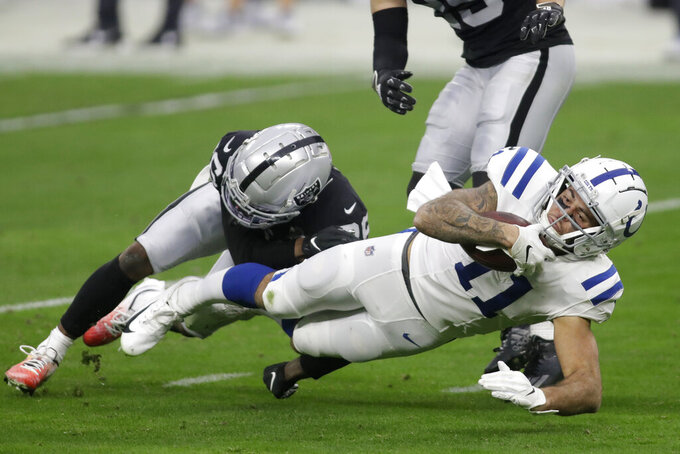 Las Vegas Raiders cornerback Nevin Lawson (26) tackles Indianapolis Colts wide receiver Michael Pittman (11) during the first half of an NFL football game, Sunday, Dec. 13, 2020, in Las Vegas. (AP Photo/Isaac Brekken)