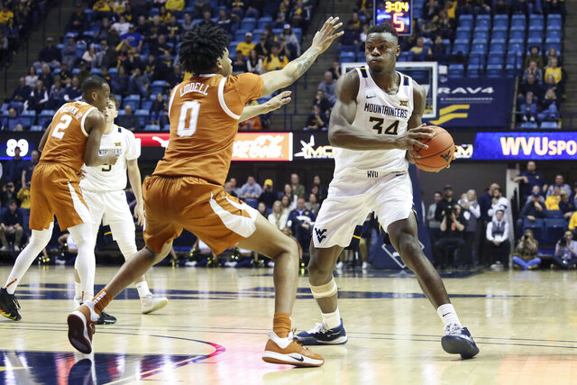 West Virginia forward Oscar Tshiebwe (34) goes to pass the ball as he is defended by Texas forward Gerald Liddell (0) during the second half of an NCAA college basketball game Monday, Jan. 20, 2020, in Morgantown, W.Va. (AP Photo/Kathleen Batten)