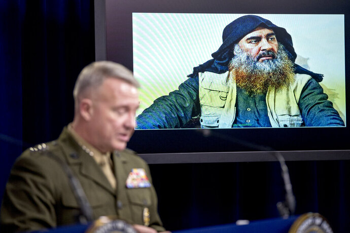Abu Bakr al-Baghdadi is displayed on a monitor as U.S. Central Command Commander Marine Gen. Kenneth McKenzie at a joint press briefing at the Pentagon in Washington, Wednesday, Oct. 30, 2019, on the Abu Bakr al-Baghdadi raid. (AP Photo/Andrew Harnik)