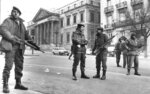 FILE - In this Feb. 1981 file photo, members of the the anti-riot squad of the National police stand guard at the square in front of the Spanish Cortes (Parliament) seen in the background, in Madrid, Spain while inside the lower house about 150 armed Civil Guards still held the deputies hostage. King Felipe VI, Spanish lawmakers and others on Tuesday, Feb.23, 2021, are marking 40 years since a paramilitary coup attempt failed to derail the country's peaceful transition to democracy. The anniversary has been obscured by the absence of Juan Carlos I, the former monarch now beset by financial scandals.  (AP Photo, File)