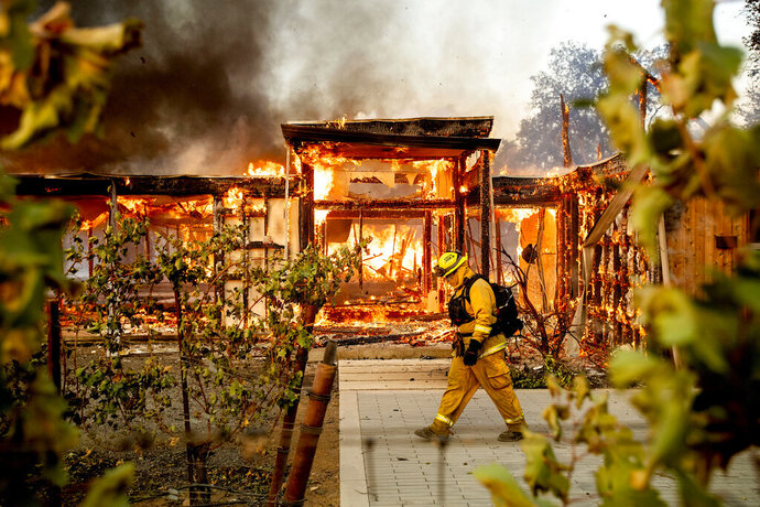 FILE - In this Oct. 27, 2019, file photo Woodbridge firefighter Joe Zurilgen passes a burning home as the Kincade Fire rages in Healdsburg, Calif.  California's massive property insurance market is feeling the effects of three straight years of damaging wildfires. Insurers have pulled out of some markets and canceled thousands of policies, forcing regulators to step in and expand a state program that homeowners often turn to as a last resort. (AP Photo/Noah Berger, File)