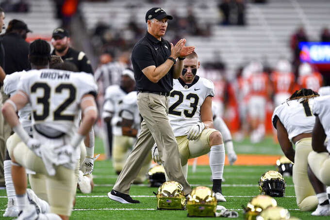 Wake Forest head coach Dave Clawson walks on the field as his players stretch before an NCAA college football game against Syracuse in Syracuse, N.Y., Saturday, Oct. 9, 2021. (AP Photo/Adrian Kraus)
