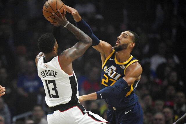 Los Angeles Clippers forward Paul George, left, shoots as Utah Jazz center Rudy Gobert defends during the first half of an NBA basketball game Saturday, Dec. 28, 2019, in Los Angeles. (AP Photo/Mark J. Terrill)