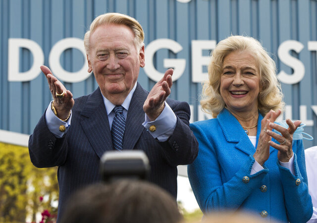 FILE - In this Monday, April 11, 2016, file photo, Los Angeles Dodgers legend Vin Scully, left, with his wife, Sandra Scully, thanks Dodgers' fans at a dedication ceremony unveiling a street sign of his namesake at the entrance to Dodger Stadium in Los Angeles. The wife of Hall of Fame announcer Vin Scully has died. The Los Angeles Dodgers say Sandra Scully died Sunday, Jan. 3, 2021, at age 76. She had been dealing with the neuromuscular disease ALS over the last several years and died at Ronald Reagan UCLA Medical Center in Los Angeles. She and Vin Scully celebrated their 47th wedding anniversary in 2020. (AP Photo/Damian Dovarganes, File)