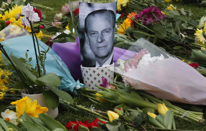 A photo of Britain's Prince Philip is among flowers left by the public outside the gates of Windsor Castle, a day after the death of Britain's Prince Philip, in Windsor, England, Saturday, April 10, 2021. Britain's Prince Philip, the irascible and tough-minded husband of Queen Elizabeth II who spent more than seven decades supporting his wife in a role that mostly defined his life, died on Friday. (AP Photo/Frank Augstein)