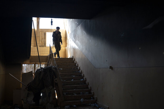 A U.S.-backed Syrian Democratic Forces (SDF) fighter walks inside a building used as a temporary base near the last land still held by Islamic State militants in Baghouz, Syria, Monday, Feb. 18, 2019. Hundreds of Islamic State militants are surrounded in a tiny area in eastern Syria are refusing to surrender and are trying to negotiate an exit, Syrian activists and a person close to the negotiations said Monday.  (AP Photo/Felipe Dana)