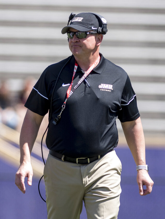 FILE - In this April 14, 2018, file photo, James Madison head coach Mike Houston watches during the team's spring NCAA college football game in Harrisonburg, Va. Houston's Dukes open the season at North Carolina State on Saturday. (Daniel Lin/Daily News-Record Via AP, File)