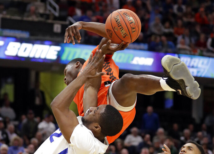 Buffalo's Dontay Caruthers, bottom, drives to the basket against Bowling Green's Daeqwon Plowden during the second half of an NCAA college basketball game for the Mid-American Conference men's tournament title Saturday, March 16, 2019, in Cleveland. Plowden was called for the foul. Buffalo won 87-73. (AP Photo/Tony Dejak)