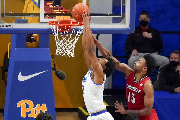 Pittsburgh's Noah Collier, left, tries to dunk as Louisville's David Johnson (13) defends during the first half of an NCAA college basketball game Tuesday, Dec. 22, 2020, in Pittsburgh. (AP Photo/Keith Srakocic)