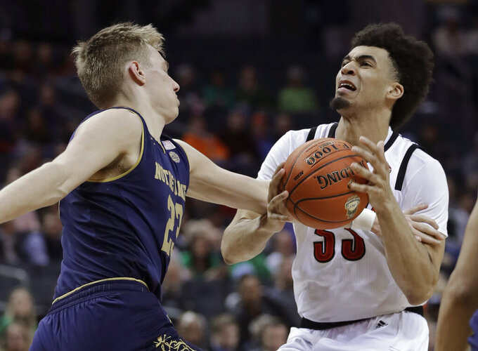Louisville's Jordan Nwora (33) is fouled by Notre Dame's Dane Goodwin (23) during the first half of an NCAA college basketball game in the Atlantic Coast Conference tournament in Charlotte, N.C., Wednesday, March 13, 2019. (AP Photo/Nell Redmond)