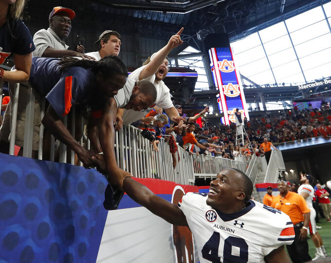 FILE - In this Saturday, Sept. 1, 2018, file photo, Auburn linebacker Montavious Atkinson (48) celebrates with he fans after their 21-16 win over Washington in an NCAA college football game in Atlanta. Proof of the SEC's strength has come in No. 9 Auburn's win over No. 10 Washington to open the season and No. 6 Louisiana State's wins over No. 21 Miami and Auburn. (AP Photo/John Bazemore, File)