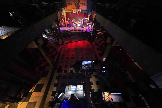 FILE - In this Oct. 26, 2020, file photo, production engineers record the band Galactic for a video stream concert, inside an empty Tipitina's music club in New Orleans. Three New Orleans music venues are going to require proof of coronavirus vaccination or a negative test to get in the club. The clubs _ Tipitina's, the Maple Leaf Bar and d.b.a. _ made the announcement late Wednesday, July 28, 2021, in a news release. The new rule will go into effect for performances at the venues this Friday. (AP Photo/Gerald Herbert)