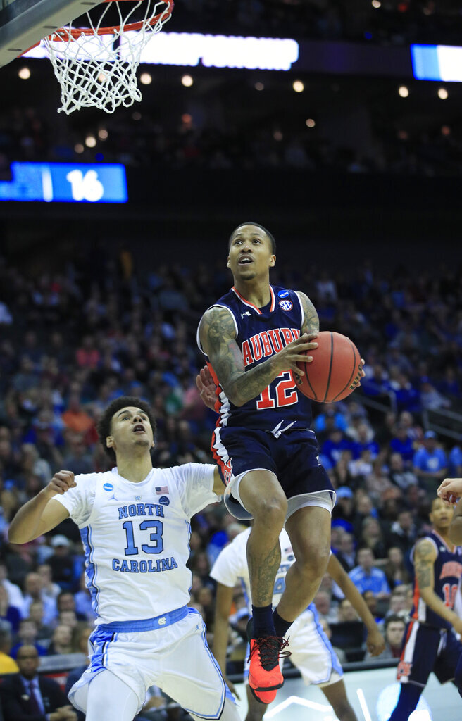 Auburn's J'Von McCormick (12) heads to the basket as North Carolina's Cameron Johnson (13) watches during the first half of a men's NCAA tournament college basketball Midwest Regional semifinal game Friday, March 29, 2019, in Kansas City, Mo. (AP Photo/Orlin Wagner)
