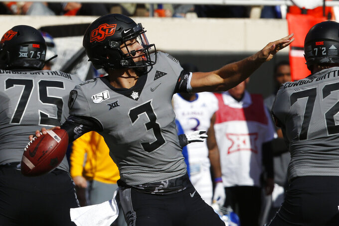 Oklahoma State quarterback Spencer Sanders (3) throws in the first half of an NCAA college football game against Kansas in Stillwater, Okla., Saturday, Nov. 16, 2019. (AP Photo/Sue Ogrocki)