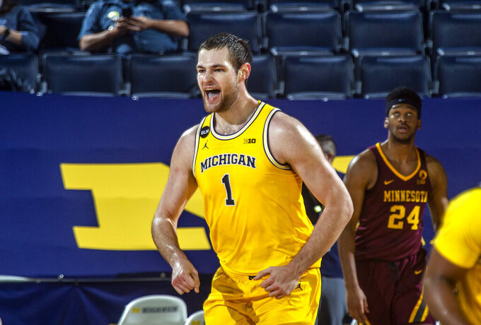 Michigan guard Franz Wagner (21) celebrates after making a dunk in the first half of an NCAA college basketball game against Minnesota at Crisler Center in Ann Arbor, Mich., Wednesday, Jan. 6, 2021. (AP Photo/Tony Ding)