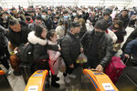 Travelers wear face masks as they line up at turnstiles at a train station in Nantong, eastern China's Jiangsu province, Wednesday, Jan. 22, 2020. The number of cases of a new virus has risen to over 400 in China and the death toll to 9, Chinese health authorities said Wednesday. (Chinatopix via AP)