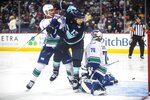 The puck sails past Seattle Kraken's Brandon Tanev (13) in the second period of an NHL preseason hockey game against the Vancouver Canucks Sunday, Sept. 26, 2021, in Spokane, Wash. (Dean Rutz/The Seattle Times via AP)