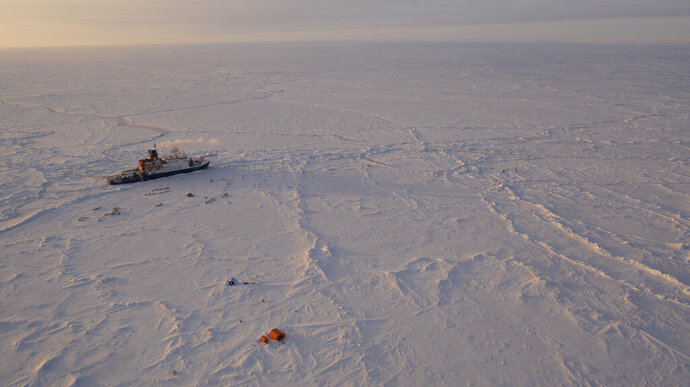 In this Friday, April 24, 2020 photo provide by the Alfred Wegener Insitute shows the German Arctic research vessel Polarstern in the ice next to a research camp in the Arctic region. Dozens of scientists are waiting in quarantine for the all-clear to join a year-long Arctic research mission aimed at improving the models used for forecasting climate change, just as the expedition reaches a crucial phase. For a while, the international mission looked like it might have to be called off, as country after country went into lockdown because of the virus, scuppering plans to bring fresh supplies and crew to the German research vessel Polarstern that's been moored in the high Arctic since last year. (Manuel Ernst/Alfred-Wegner-Institut via AP)