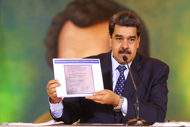In this photo released by the Venezuela's Miraflores presidential press office, President Nicolas Maduro accuses opposition leader Juan Guaido of being behind a military raid designed to oust him, as he holds a copy of a written agreement that allegedly bears Guaido's signature as evidence, during an online press conference in Caracas, Venezuela, Wednesday, May 6, 2020. (Miraflores Palace presidential press office via AP)