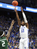 Kentucky's Keion Brooks Jr. (12) shoots while defended by UAB's Tamell Pearson (2) during the first half of an NCAA college basketball game in Lexington, Ky., Friday, Nov. 29, 2019. (AP Photo/James Crisp)