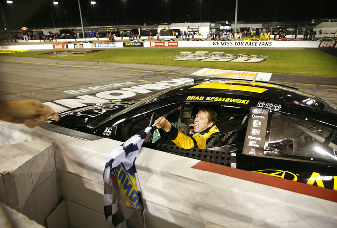 Brad Keselowski collects the checkered flag after winning a NASCAR Cup Series auto race Saturday, Sept. 12, 2020, in Richmond, Va. (James H. Wallace/Richmond Times-Dispatch via AP)