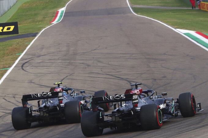 Mercedes driver Lewis Hamilton of Britain and Mercedes driver Valtteri Bottas of Finland make an honor lap next to each other after taking first and second place in the Emilia Romagna Formula One Grand Prix, at the Enzo and Dino Ferrari racetrack, in Imola, Italy, Sunday, Nov. 1, 2020. (Davide Gennari/Pool Photo)