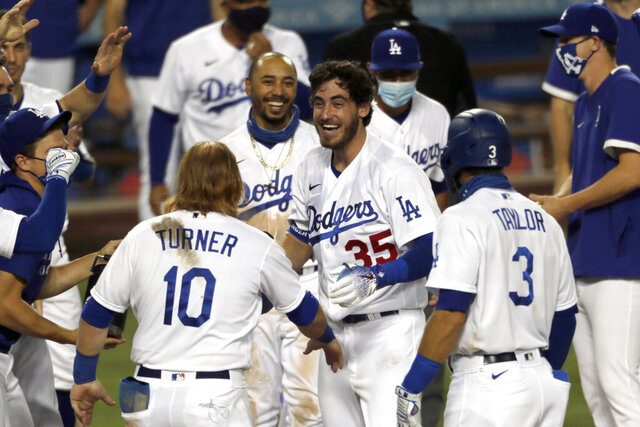 Los Angeles Dodgers' Cody Bellinger, center, celebrates with teammates at the plate after hitting a game-ending home run during the ninth inning of the team's baseball game against the Colorado Rockies in Los Angeles, Saturday, Aug. 22, 2020. The Dodgers won 4-3. (AP Photo/Alex Gallardo)