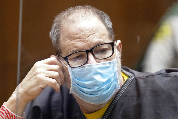 Harvey Weinstein, the 69-year-old convicted rapist and disgraced movie mogul, wears a face mask behind a protective plexiglass screen as he listens in court during a pre-trial hearing in Los Angeles, Thursday, 29 July 2021. Weinstein pleaded not guilty Wednesday to four counts of rape and seven other sexual assault counts in California.(Etienne Laurent/Pool Photo via AP)