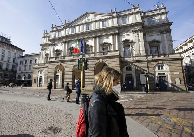 FILE - In this Monday, Feb. 24, 2020 filer, a woman wearing a sanitary mask walks past La Scala Opera house in Milan, Italy. Milan's famed La Scala opera house on Thursday, May 7, 2020 unveiled a virtual journey through the storied theater and its  archives with Google Arts & Culture in what turned out to be a strangely ideal moment:  with theaters throughout Italy and the western world closed due to coronavirus. (AP Photo/Luca Bruno, File)