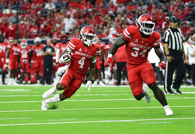 Houston running back Ta'Zhawn Henry (4) runs the ball against Texas Tech during the first half of an NCAA college football game Saturday, Sept. 4, 2021, in Houston. (AP Photo/Justin Rex)