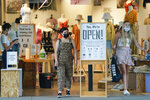 Customers leave Urban Outfitters with their purchases as they shop at Pacific City shopping mall on Tuesday, May 26, 2020, in Huntington Beach, Calif. (AP Photo/Ashley Landis)