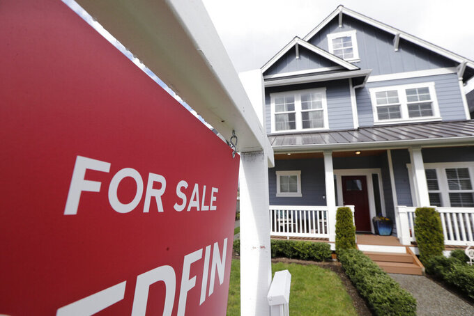 """FILE - In this April 1, 2020 photo, a """"For Sale"""" sign stands in front of a home that is in the process of being sold in Monroe, Wash., outside of Seattle.  Sales of new homes jumped again in July, rising 13.9% as the housing market continues to gain traction following a spring downturn caused by pandemic-related lockdowns. The Commerce Department reported Tuesday, Aug. 25,  that July's gain propelled sales of new homes to a seasonally-adjusted annual rate of 901,000.  (AP Photo/Elaine Thompson, File)"""