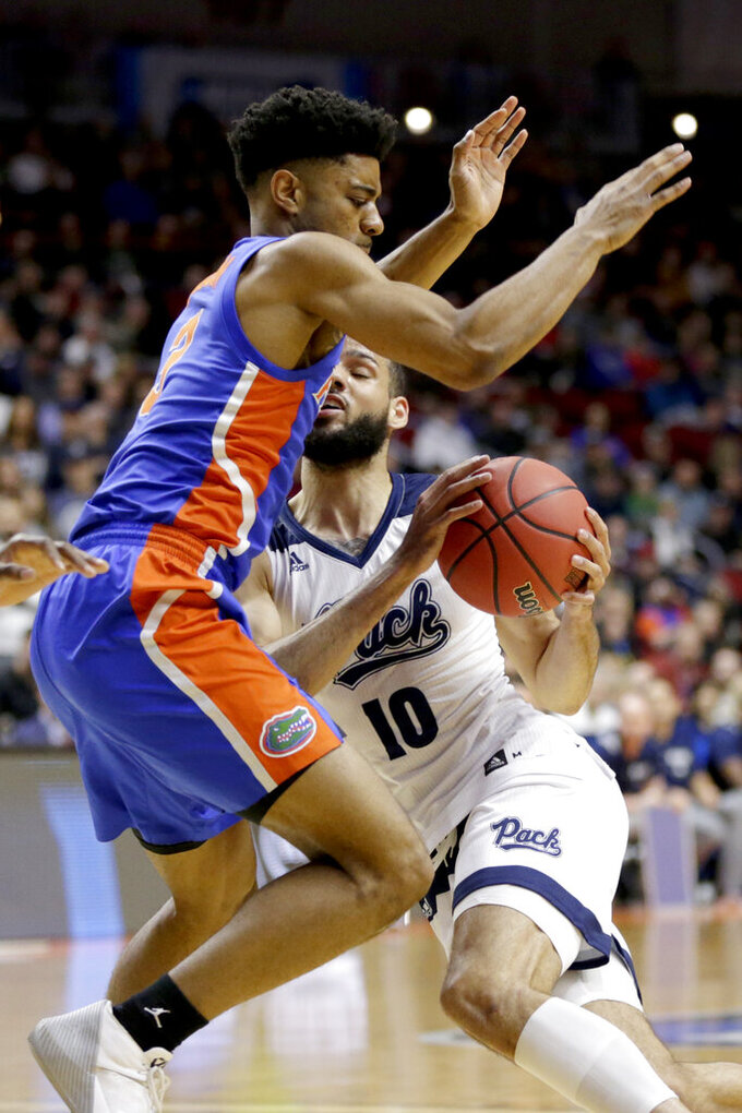 Nevada's Caleb Martin (10) tries to get past Florida's Jalen Hudson (3) during the first half of a first round men's college basketball game in the NCAA Tournament in Des Moines, Iowa, Thursday, March 21, 2019. (AP Photo/Nati Harnik)