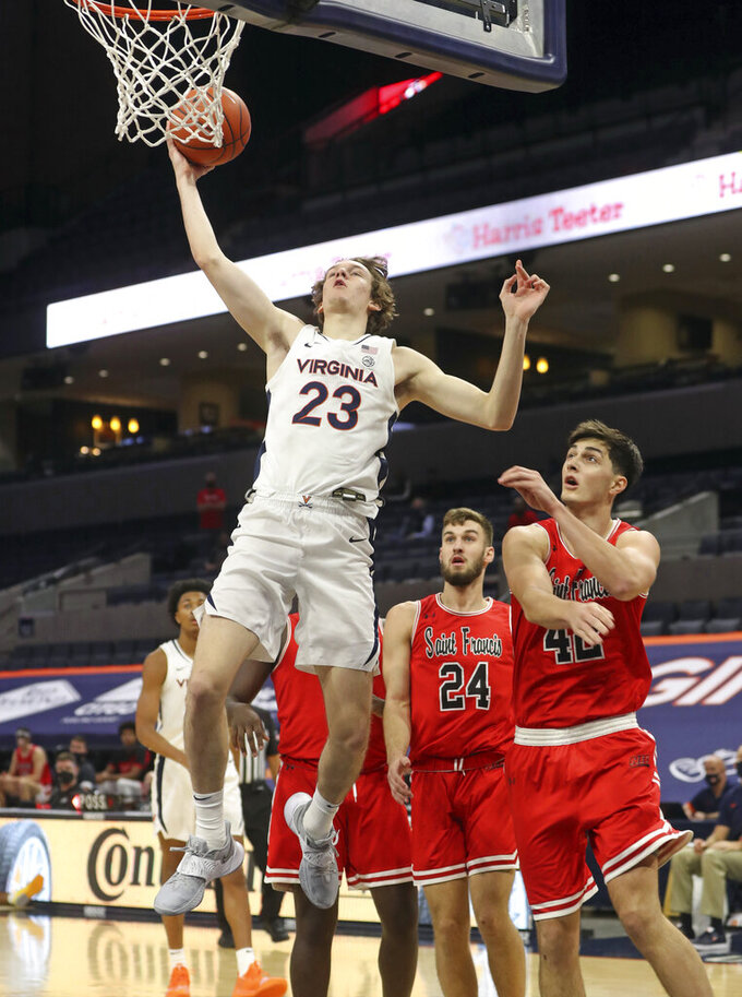 Virginia guard Kody Stattmann (23) shoots next to St. Francis forward Mark Flagg (42) and guard Bryce Laskey (24) during an NCAA college basketball game Tuesday, Dec. 1, 2020, in Charlottesville, Va. (Andrew Shurtleff/The Daily Progress via AP)